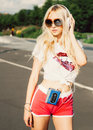 Outdoor summer fashion stylish portrait of young pretty sexy blonde girl posing in vinage sunglasses and listening to music with h Royalty Free Stock Photo