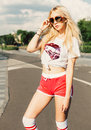 Outdoor summer fashion stylish portrait of young pretty sexy blonde girl posing in vinage sunglasses, t-shirt and red shorts. Sola Royalty Free Stock Photo