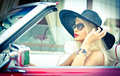 Summer portrait of stylish blonde vintage woman with long legs posing near red retro car. fashionable attractive fair hair female