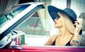 Outdoor summer portrait of stylish blonde vintage woman driving a convertible red retro car fashionable attractive fair hair girl Royalty Free Stock Photos