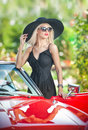 Outdoor summer portrait of stylish blonde vintage woman posing near red retro car fashionable attractive fair hair female with Stock Image