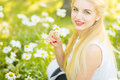 Outdoor summer portrait of young pretty cute blonde girl beautiful woman posing in the park Stock Photos