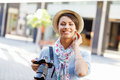 Outdoor summer smiling lifestyle portrait of pretty young woman with camera Royalty Free Stock Photo