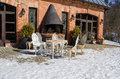 Outdoor table chairs restaurant fireplace snow retro decorative and near building between in winter Royalty Free Stock Image