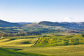 Outdoor tuscan val d orcia green and yellow hills view with blue sky Stock Photo