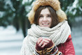 Outdoor winter portrait of cheerful young lady holding tourist vacuum flask cup with hot drink Royalty Free Stock Photo
