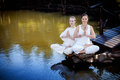Outdoor yoga session in beautiful place by a lake meditation garden with two women meditating Royalty Free Stock Photo