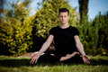 Outdoor yoga session in beautiful place meditation garden young man meditating Royalty Free Stock Photo