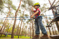 Outdoors adventure games smiling little boy walking on a rope in a park Stock Photo