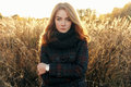 Outdoors noon portrait of serious young beautiful redhead woman in scarf and jacket on faded meadow background Royalty Free Stock Photo