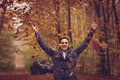 Outdoors portrait of happy young man standing in autumn park at Royalty Free Stock Photo