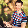 Outdoors portrait men with laptop man in sunny day in park Stock Photos