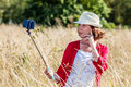 Outdoors selfie for beautiful s woman in high dry grass making her self portrait on mobile phone on stick the middle of summer Stock Images