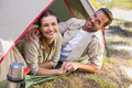 Outdoorsy couple smiling at camera inside their tent Royalty Free Stock Photo