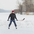 Outdor portrait of young hokey player with stick on a frozen river dnepr ukrainednepropetrovsk ukraine february Royalty Free Stock Images