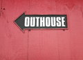 Outhouse sign with arrow on a red wooden wall Royalty Free Stock Photo