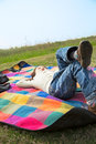 Outing girl lying on a picnic mat under the blue sky Stock Photo