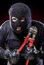 Outlaw a burglar wearing a balaclava holding huge wire cutters over black background Stock Photography