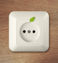 Outlet on wooden wall with leaf go green power concept Stock Photo