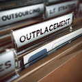Outplacement concept folder and focus on a tab with the word blur effect of company downsizing Royalty Free Stock Images