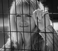 Outside looking in woman trapped on of metal fence inside Stock Image
