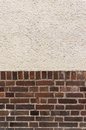 Outside wall with plastered top on red clinker brick bottom Royalty Free Stock Photo