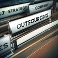 Outsoucing strategy folder tab with focus on the the word outsourcing contracting out or subcontracting concept image with blur Stock Image
