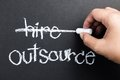Outsource hand delete hire word on blackboard with chalk for business outsourcing concept Stock Images