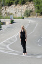 Outstanding model with a slim body do a fashion shooting on the high speed road wearing black neck jumpsuit Royalty Free Stock Image