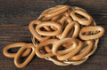 Oval bagels in plate wicker bowl on old wooden background top view Royalty Free Stock Images