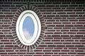 Oval window in brick wall Stock Photos