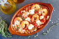 Oven backed prawns with feta, tomato, paprika, thyme in a traditional ceramic form on a abstract background. Healthy eating concep Royalty Free Stock Photo