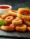 Oven baked breaded calamari rings served with lime wedges, sweet chilli sauce and mayonnaise Royalty Free Stock Photo
