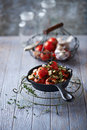Oven baked cherry tomatoes with garlic and feta cheese in a cast iron pan Royalty Free Stock Images