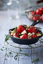 Oven baked cherry tomatoes with garlic and feta cheese in a cast iron pan Royalty Free Stock Image