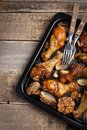 Oven baked chicken legs with onions, garlic and peppers on a dark wooden background closeup. Top view with copy space Royalty Free Stock Photo