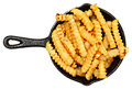 Oven baked crinkle fries in cast iron skillet over white Stock Photos