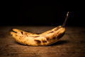 Over ripe spotted banana on wood surface Stock Photography