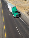 Over the road transport semi truck hauling cargo containier a shot from above a california freeway and local transporting Royalty Free Stock Photography