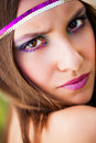 Over the shoulder young brunette model staring with a slight frown her wearing bright plum make up and a purple and gold headband Stock Image