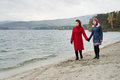 Overcast day beauty mature women in red topcoat with young daughter walking outdoor on water moorage for boat in autumn cold Royalty Free Stock Images