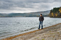 Overcast day young guy outdoor on water moorage for boat in autumn cold Royalty Free Stock Photo
