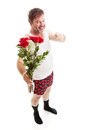 Overconfident scruffy guy with flowers looking in his underwear too much confidence holding a vase of red roses and pointing at Royalty Free Stock Photo