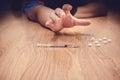 Overdose male drug addict hand drugs narcotic syringe on floor Royalty Free Stock Image