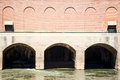 Overflow conduits in brick dam concrete arched under an old hydroelectric Stock Images