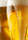 Overflowing glass of golden ale Royalty Free Stock Photo