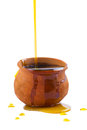 Overflowing honey pot pouring into an clay isolated on a white background Royalty Free Stock Photography