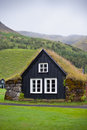 Overgrown typical rural icelandic house at overcast day misty Stock Photography