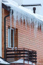 Overhanging icicles house roof Stock Photo