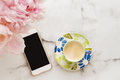 Overhead of coffee, mobile phone and flowers Royalty Free Stock Photo